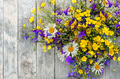 Wooden background with a bouquet of small wild flowers daisies, bells . Stock Images