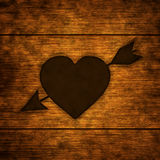 Wooden background with burnt heart Stock Images