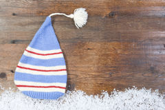 Wooden background with  cap, snow on the border and copyspace Stock Photo