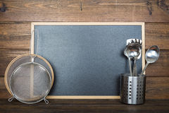 Wooden background with a chalkboard and cooking utensils Stock Images