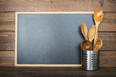 Wooden background with a chalkboard and cooking utensils Stock Photos