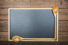 Wooden background with a chalkboard and cooking utensils Stock Image