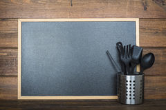 Wooden background with a chalkboard and cooking utensils Royalty Free Stock Images