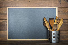 Wooden background with a chalkboard and cooking utensils Royalty Free Stock Image