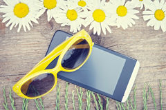 Wooden background with chamomile flowers, sunglasses and mobile Stock Photo