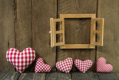 Wooden background: checked hearts of fabric and window frame. Stock Photos