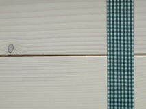 Wooden background with a checked ribbon Royalty Free Stock Photo