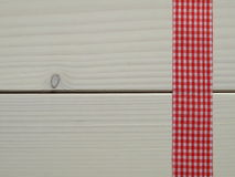 Wooden background with a checked ribbon Royalty Free Stock Images