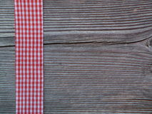 Wooden background with a checked ribbon stock images
