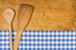 Wooden background with a checkered tablecloth and wooden spoon. Wooden background with a blue checkered tablecloth and wooden spoon Stock Photography