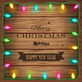 Wooden background with christmas lights and vintage typography sign Royalty Free Stock Photos