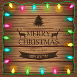 Wooden background with christmas lights and vintage typography sign  Royalty Free Stock Photography