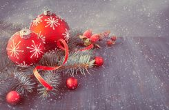 Wooden background with Christmas tree twigs decorated with Xmas. Baubles, ribon and frosted berries. Space for your text, filtered image Stock Photo
