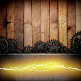 Wooden background with cogwheel gears and electric lightning Stock Photography