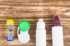 On a wooden background contact lenses in a container and bottles with care products royalty free stock photos