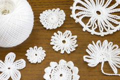 Wooden background with cotton crochet lace white flowers. stock image
