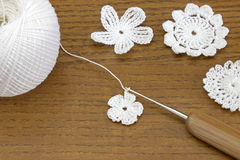 Wooden background with cotton crochet lace white flowers and crochet hook. royalty free stock photo