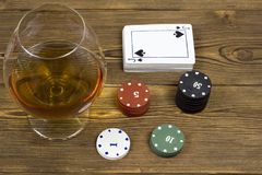 On a wooden background is a deck of cards and a glass of alcohol, gambling royalty free stock images
