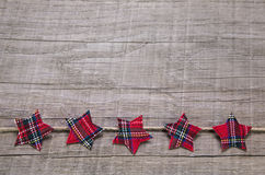 Wooden background decorated with red christmas stars of fabric. Stock Photography
