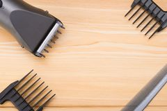 Wooden background, an electric machine for cutting hair and a set of nozzles to it. in the center there is a place for the inscrip. On a wooden background, an stock photography