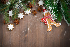 Wooden background with fir branches, cookies and gingerbread man. Top view, close-up Stock Photography