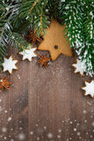 Wooden background with fir branches, cookies and snow bokeh Royalty Free Stock Photography