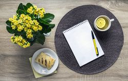 On a wooden background a flower of yellow color kalandive napkin round wicker tea cup lemon saucer puff croissant breakfast Stock Photos