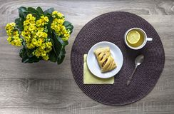 On a wooden background a flower of yellow color kalandive napkin round wicker tea cup lemon saucer puff croissant breakfast Royalty Free Stock Photography