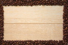 Wooden background with frame of coffee beans stock photos