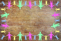 Wooden background with frame made of multicolored paper people Royalty Free Stock Image