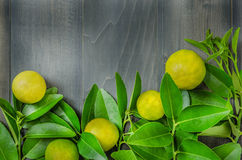 Wooden background with fresh lime and green leaves Royalty Free Stock Photo