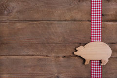 Wooden background with good luck pig on checkered ribbon or adve Stock Photo