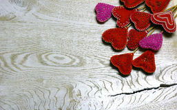 Wooden background with handmade felt hearts on light wooden background. Stock Photography