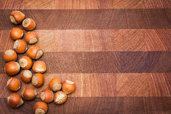 Wooden  background with hazelnuts and copy space. Wooden  surface  with hazelnuts and copy space. Handful of hazelnuts disposed from left side. Right side can be Stock Photos