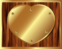 Wooden background with a heart of gold Stock Images