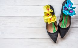 Wooden background with lady shoes and paper flowers inside. women and mother day concept. ecology crafts as a present. stock image