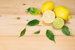 wooden background lemon leaves with cut fruits in a corner Royalty Free Stock Photos