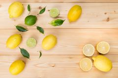 On a wooden background, lie different lemons in order along with green lime royalty free stock photo