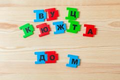 On a wooden background lie the letters of the Russian alphabet. The child laid out the inscription of the house in Russian.  royalty free stock photos