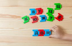 On a wooden background lie the letters of the Russian alphabet. A child spends word home in Russian stock images