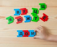 On a wooden background lie the letters of the Russian alphabet. A child spends word home in Russian.Square.  stock photos
