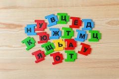 On a wooden background lies a group of letters of the Russian alphabet.  stock photo