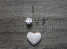 On a wooden background lies the paper clip word love instead of letter o paper lumpy crumpled cookie heart with mastic Royalty Free Stock Photos