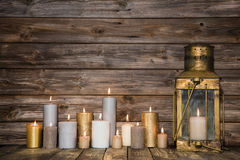 Wooden background in with many burning candles and a old rustic. Wooden vintage background in with many burning candles and a old rustic lantern stock photo