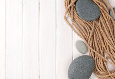 Wooden background with marine rope and sea stones Stock Photos
