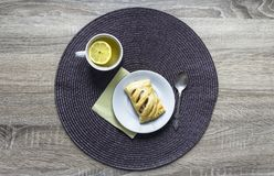 On a wooden background napkin round wicker tea cup lemon saucer puff croissant breakfast Royalty Free Stock Photography
