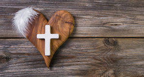 Wooden background with olive heart and white cross for an obitua Royalty Free Stock Image