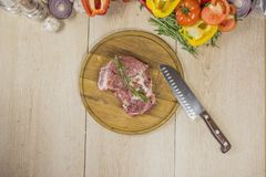 A wooden background with organic vegetables on its side, in the center a pickled meat on a wooden board and a rosewood Stock Image