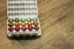 On a wooden background packing of eggs. different colors. top view royalty free stock photos