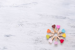 Wooden background painted with white paint with colorful hearts. Hearts clothespins. The texture of the tree. Royalty Free Stock Photos